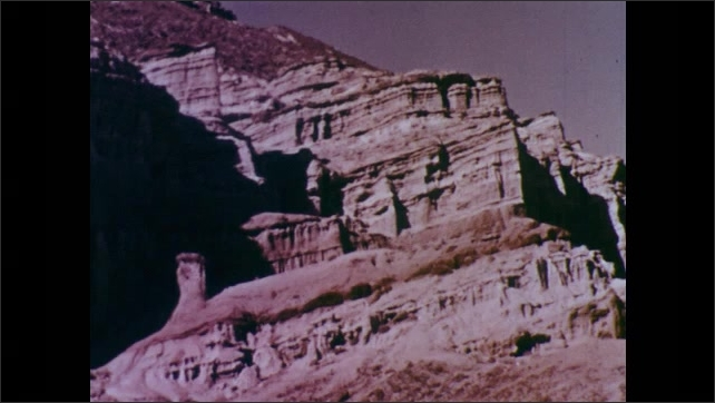 1960s: UNITED STATES: cutting action of sand on hard rocks. Rock cliff shaped by sand and dust