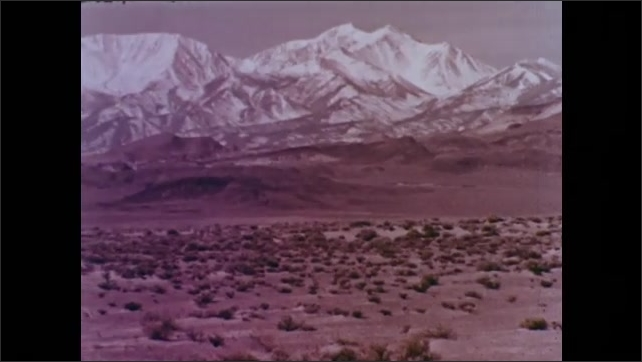 1960s: UNITED STATES: air and wind in valley. Snow on mountains. Bird glides in sky. Kite and tail.