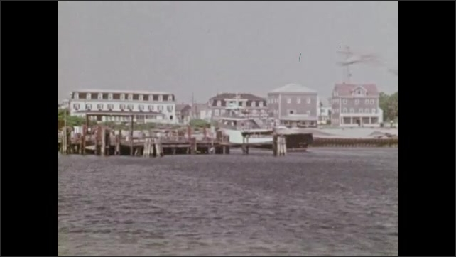 1970s: Small village along waterfront and rocky beach. Buildings in village. Warehouse buildings.