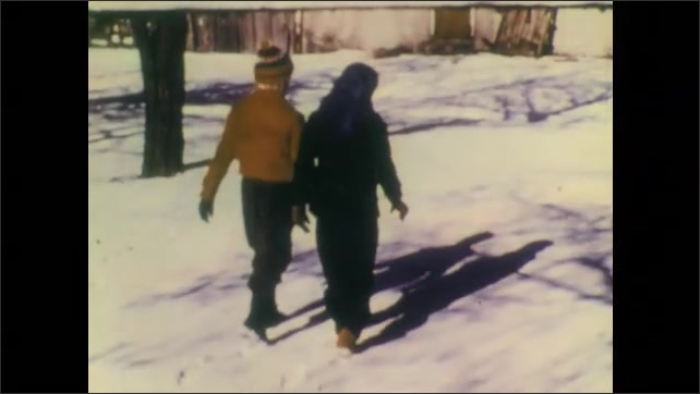 1940s: Children leave footprints in snow. Children stop and look down in snow. Girl smiles. Animal tracks in snow.