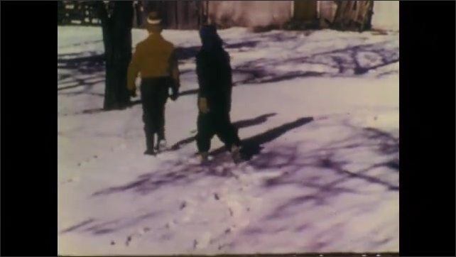 1940s: Rabbit peers from burrow. Rabbit runs across snowy field. Children walk through snowy lawn. Children walk past barn and enter storage shed. Boy removes axe from shed.