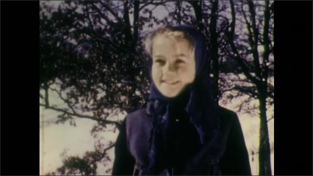 1940s: Boy and girl walk toward pine trees. Girl smiles and speaks. Boy chops down small pine tree with axe.