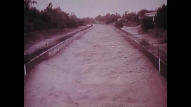 1970s: Water spills over dam. Water runs through canal through Los Angeles. People stand on overpass, watch water. Destruction of Hollywood sign.