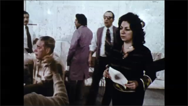 1970s: Men and women talk on phones and look at papers.
