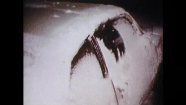 1970s: Tow truck sits in road, lights flash. Man trudges through snow, past buried cars. Man brushes snow off car windows, look inside. Men push car.