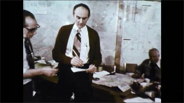 1970s: Man talks on telephone. People in office look at papers, talk, look at map.