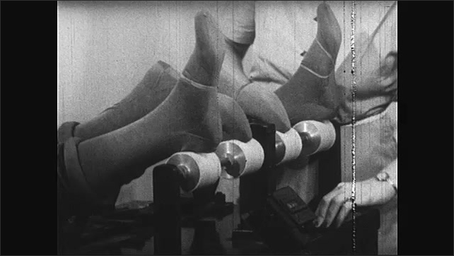 1940s: Woman operates machine that tests wear on silk stockings. Sample stockings on mannequin feet are run over rollers.