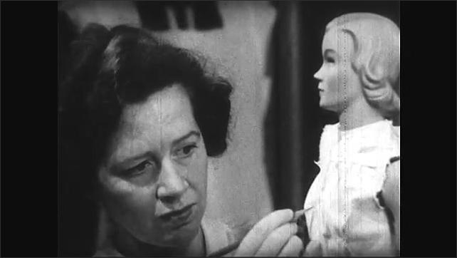 1940s: Woman draws outline of woman's uniform. Woman creates model of woman's uniform on doll. Woman dresses in uniform.