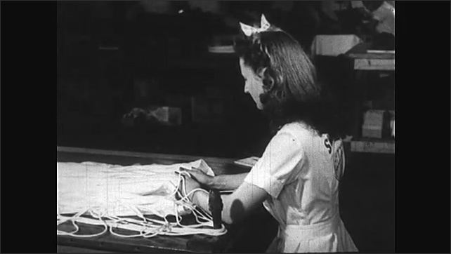1940s: Women work in factory, sew and assemble parachutes. Woman looks through microscope.