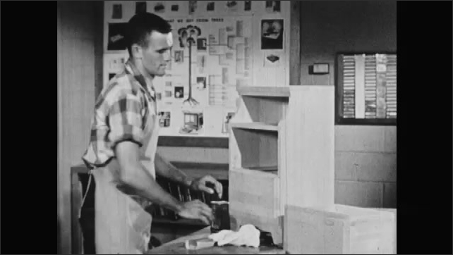1950s: UNITED STATES: paint pots in cupboard. Hand shows wood samples to camera. Wood finishes in cabinet. Man puts drawer in wooden drawer.