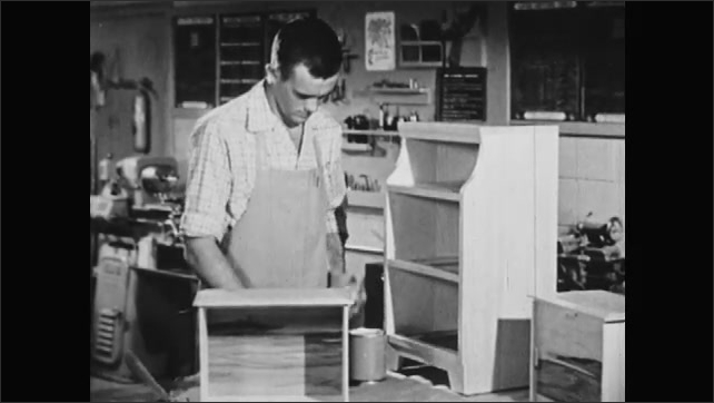 1950s: UNITED STATES: student prepares wood for paint finish. Man opens tin of paint. Brush covers knots in wood.