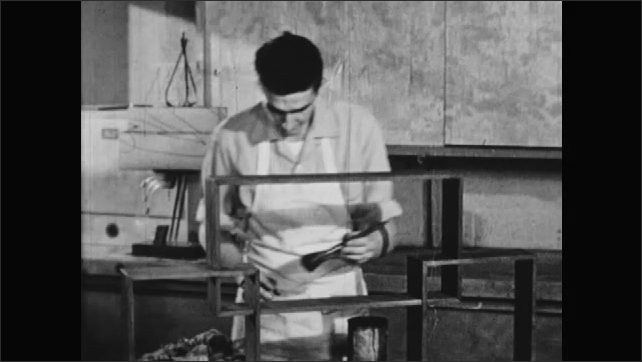 1950s: UNITED STATES: hand wipes oil from wood. Man paints shelf with oil stain. Man uses brush to paint wood. Shellac in container. Paste filler in jar.