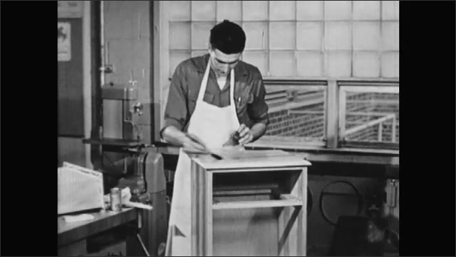 1950s: UNITED STATES: man applies lacquer to wood.