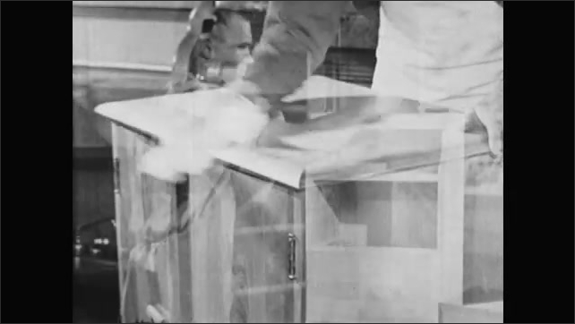 1950s: UNITED STATES: man applies paste wax to finished project. Man finishes wooden project in shop