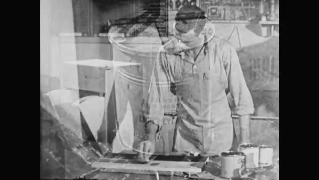 1950s: UNITED STATES: man paints wood with stain in workshop. Foot on pedal bin. Oily rags disposed of in metal container