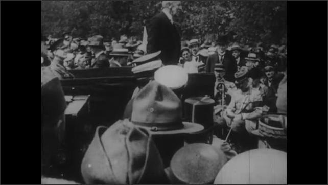 1950s: President Wilson speaks to crowd. Wilson shakes hands in cemetery.