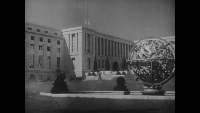 1950s: Small group of men stand around and listen to man talk. Group disperses. U.S. Capitol dome and flag at half mast. Palace of Nations building.