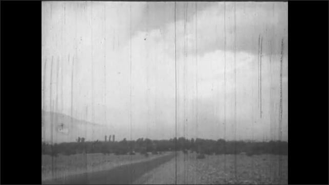 1950s: UNITED STATES: clouds in sky above ground. Palm tree leaves against sky
