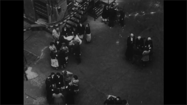 1950s: Men and women stand in circle, talk, walk away. People stand in groups and talk. Man motions people over. Large group gathers in a circle and talks.