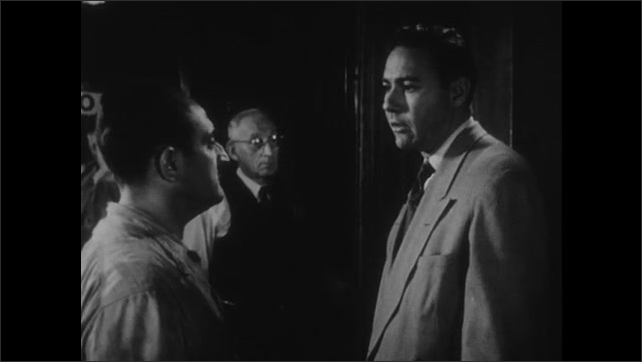 1950s: Man exits elevator, talks to man in hallway. Close up of men talking. Man enters elevator, man walks away. Man takes off shirt.
