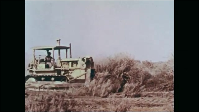 1960s: UNITED STATES: farmers plan land ready for reservoir. Desert sage brush in field. Tractor clears land for use.