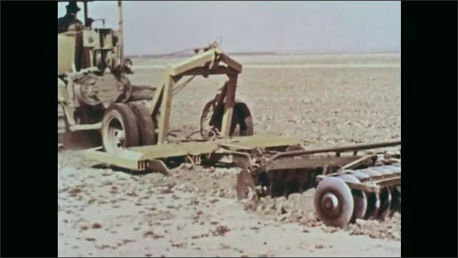 1960s: UNITED STATES: machine planes landscape ready for farming industry. Tractor and plough in field. Builders construct dam.