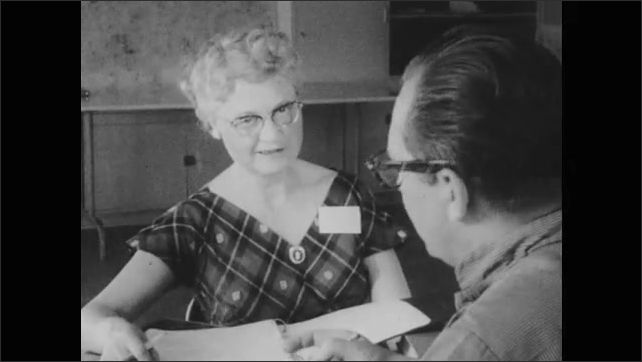 1950s: man and woman seated at table talking about notes, woman standing up to address group