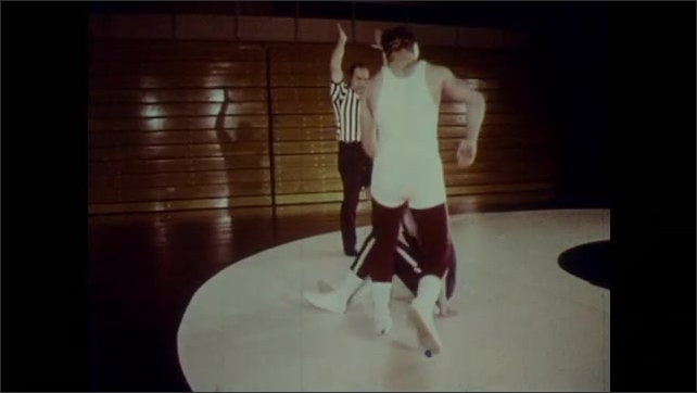 1970s: Two wrestlers on mat wrestle. One wrestler throws the other to the mat as the ref watches. Two wrestlers grapple with each other.