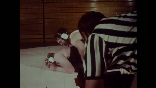 1970s: Two wrestlers grapple on mat. One wrestler tries to pin the other.