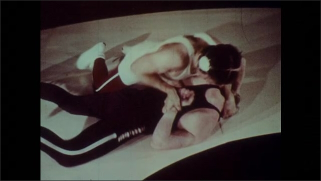 1970s: Two wrestlers grapple on mat. Wrestler places hold on opponent's arm behind back. Ref calls foul. The break hold and stand up.