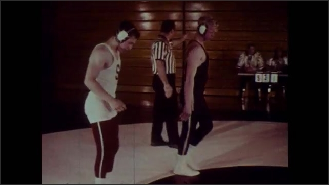 1970s: Spectators watch wrestling match. Two wrestlers grapple on hands and knees on mat. Ref calls match. Two opponents stand face to face. Ref declares winner. Wrestlers leave.