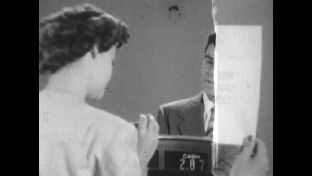 1950s: Man standing in front of register hands woman behind register a bottle of nail polish. Woman reads letter, begins interview with prospective employee.