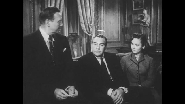 1950s: Formal drawing room, men and woman sit on sofa, man talks confidently, looks satisfied, looks at others. Priest talks, stands up, walks across room.