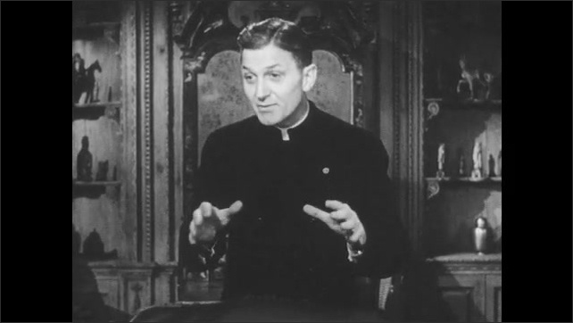 1950s: Father Keller stands behind high-backed chair and speaks earnestly and with hand gestures.
