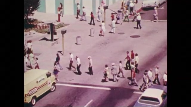 1970s: Slow motion, lawnmower cutting grass. High angle view, people crossing intersection. Low angle view of building, sun.