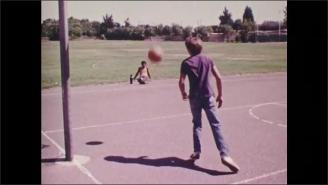 1970s: View of digital thermometer. Boy playing basketball, boy sitting in background. Slow motion, low angle view of boy playing basketball.