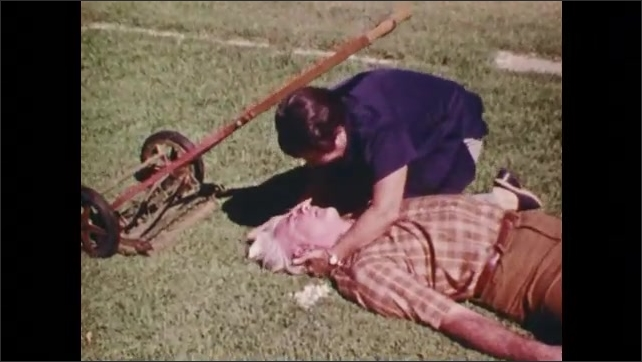 1970s: Ambulance pulls up to curb. Zoom in, woman with man on ground, medic examines man.