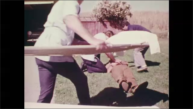 1970s: Close up of man on ground. Man pulls over stretcher, carries stretcher to man. Medics put man on stretcher.