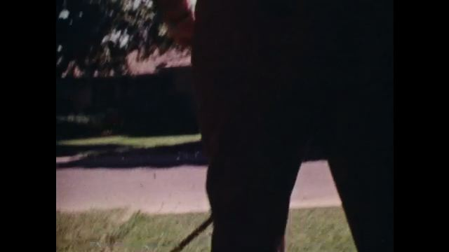 1970s: Man mowing lawn, tilt down to lawnmower. Close up of thermometer. Man mowing lawn. Zoom in, close up of lawnmower.