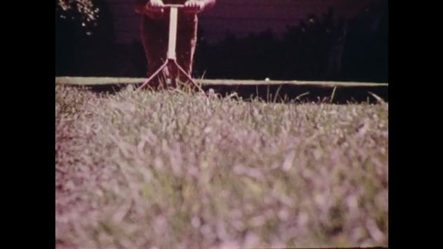 1970s: Slow motion, lawnmower cutting grass.