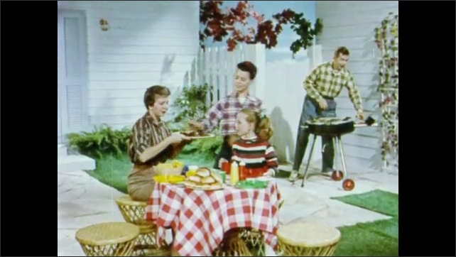 1950s: Mother and daughter sit at outdoor table, father and son grill food. Boy brings plate of burgers to table, sits down, father sits down at table. Family talks and prepares plates.