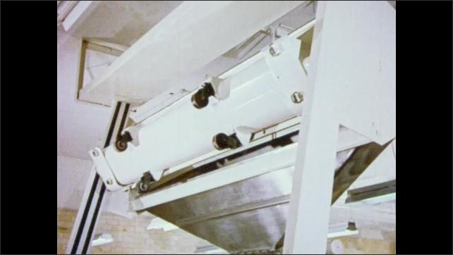 1950s: Man places gauge into large trough full of dough. Dough rises. Machine lifts up trough, dumps dough into vat. Machine divides dough into loaf sized pieces.