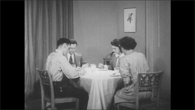 1950s: Woman talks and boy stands. Family eats dinner together. Boy stands, but sister stops him, standing and grabbing a book and bringing it to the table.
