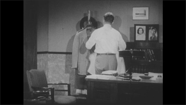 1950s: Doctor sits at desk and talks on telephone.  Man hangs up.  Man takes off and hangs up coat.  Man walks up steps.  Man rings doorbell.