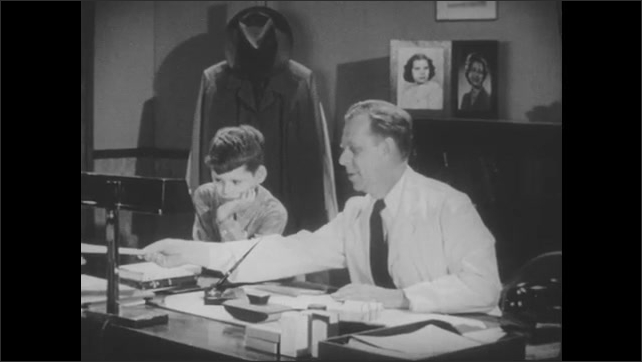 1950s: Boy stands next to doctor.  Man sits and writes.  Man hands paper to woman.  Mother reads paper.  Son puts arm around mother.  Doctor stands and goes to door.