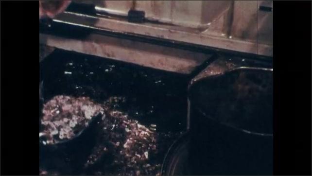 1970s: Woman sews fabric in textile workshop. Man shovels metal shavings into trash barrel.