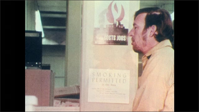 1970s: Cigarette falls from box onto paper waste and starts fire. Man smokes near smoking permitted sign. Man ties extension cord around metal pipes.