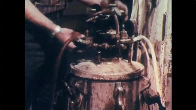1970s: Chemical canisters and drums in storage room. Man unlocks machine container and pours lacquer into tank.