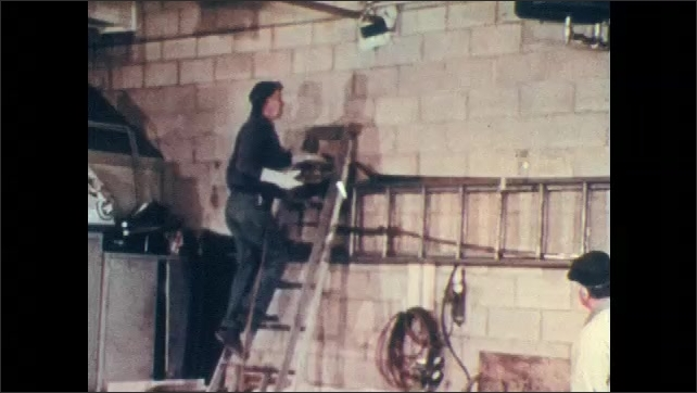 1970s: Fire officer reprimands worker and points to boxes near furnace. Man carries lit welding torch up ladder. Torch blows flame onto metal pipe.