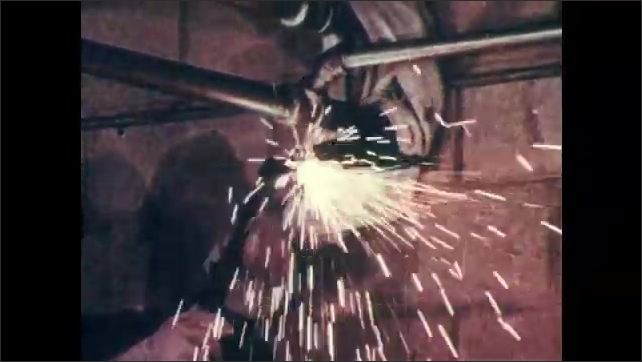 1970s: Worker stands ready near fire extinguishers. Welding torch cuts into metal and produces sparks. Sparks dance across fabric. Man stands ready with extinguishers.